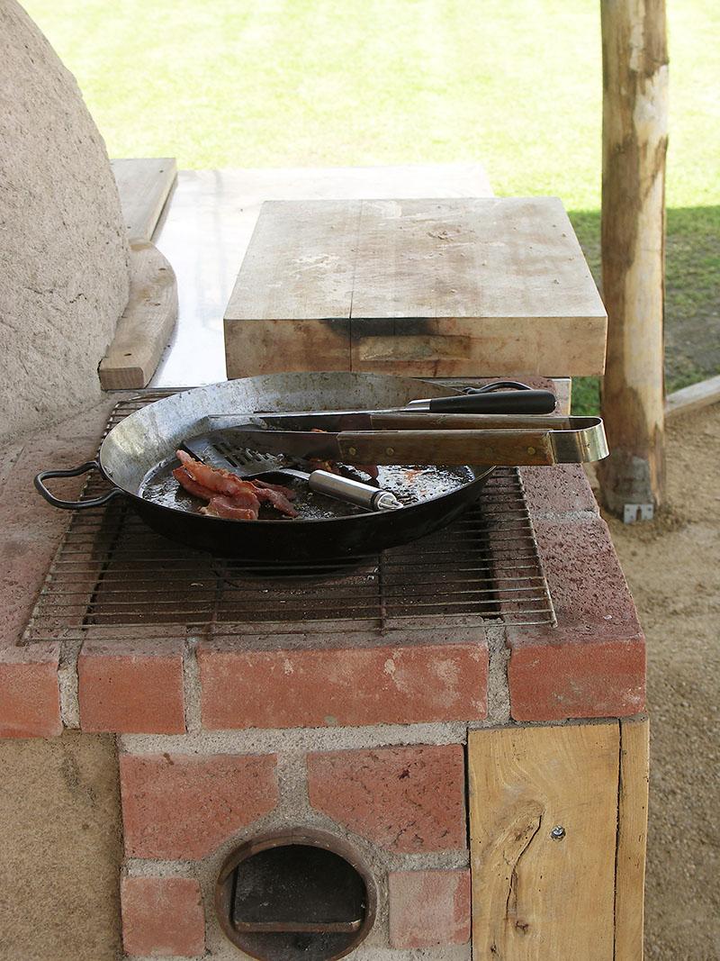 Bespoke rocket stove adjacent to earth oven