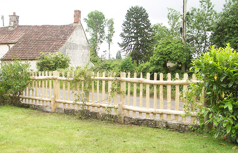 Cleft chestnut picket fence with sawn oak posts viewed from the garden