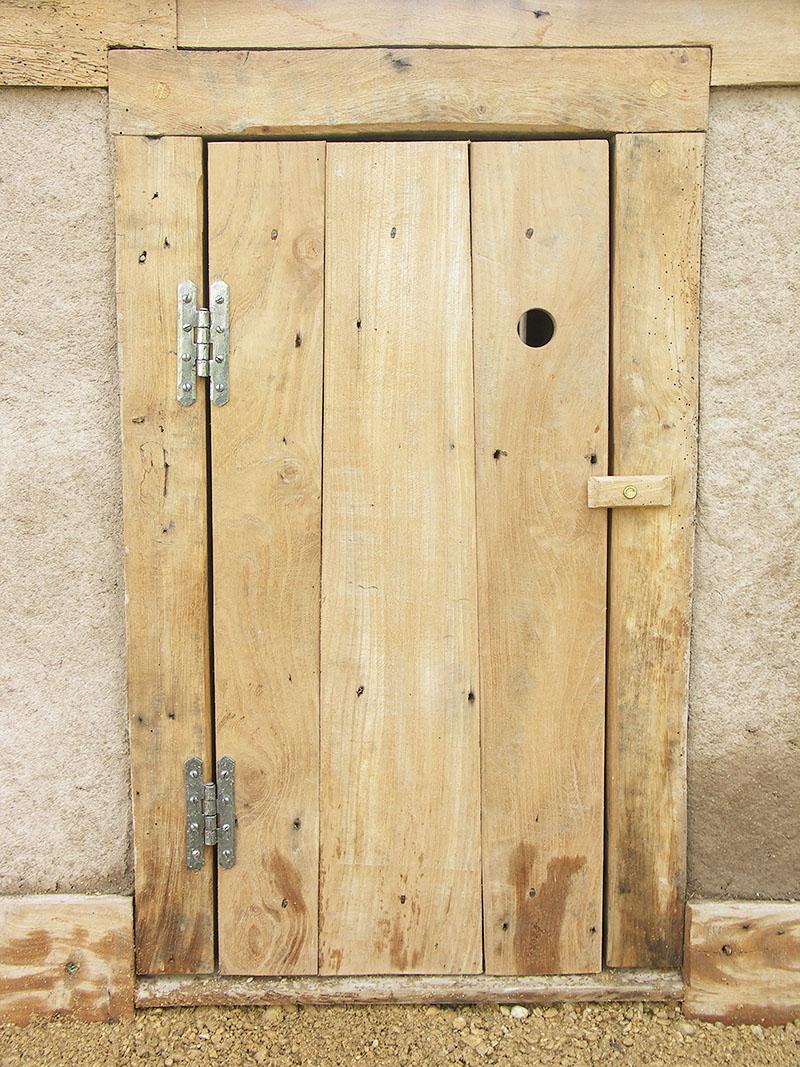 Reclaimed-elm bespoke door to cupboard under earth oven